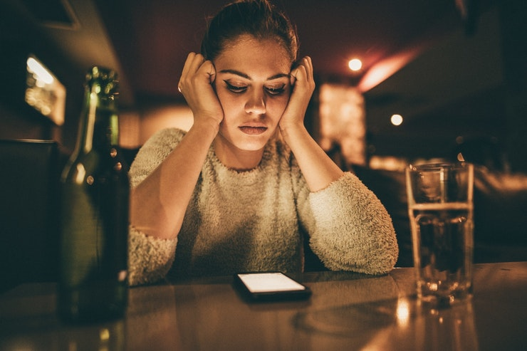 Depressed Woman Looking At Phone Message Istock 673833314