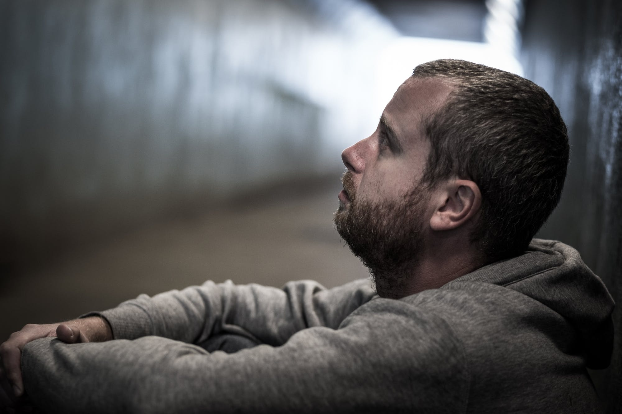 Homeless Adult Male Sitting In Subway Tunnel Begging For Money Med