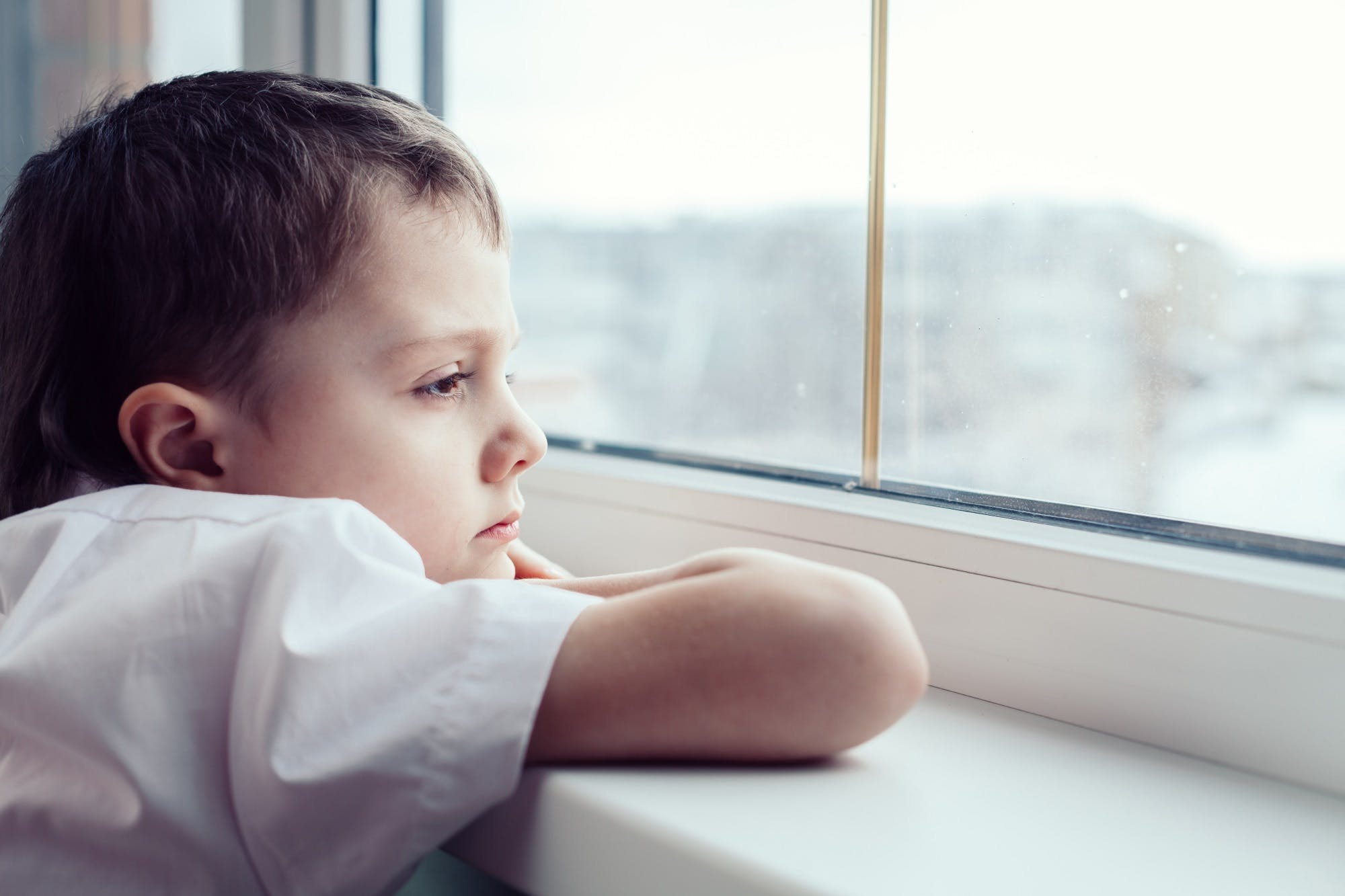 Sad Little Boy Sitting Near The Window Istock 886423602
