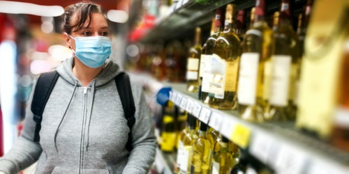 Woman buying wine with mask on